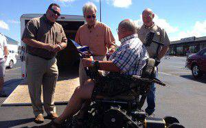 POAM Staff Members Give Action Trackchair to Nels Larsen
