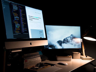 Two desktop computer screens in a dark office | Web Design Industry Trends