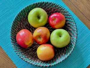 A bowl filled with red and green apples on a blue placemat on a brown wooden table | Hick's Law