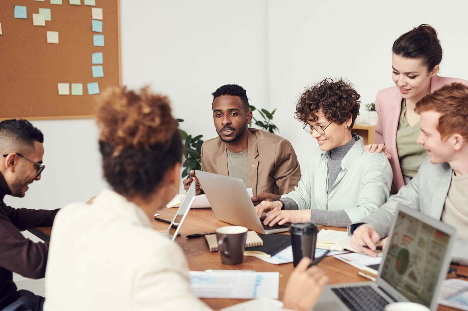 A group of people sitting around a conference room talking to each other | Jakob's Law